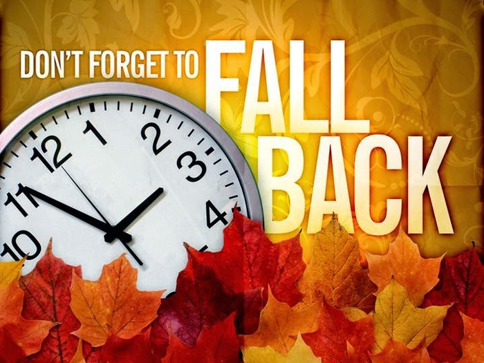 "A clock in a pile of leaves with the reminder ""Don't forget to fall back"" for daylight savings time."