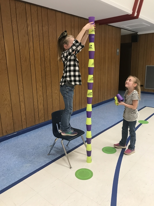 Students stacking cups on top of one another. One is standing on a chair to reach the top of the tower.