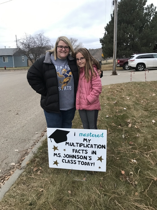 "Teacher and student standing in front of sign stating ""I mastered my multiplication facts in Ms Johnson's class today!"""