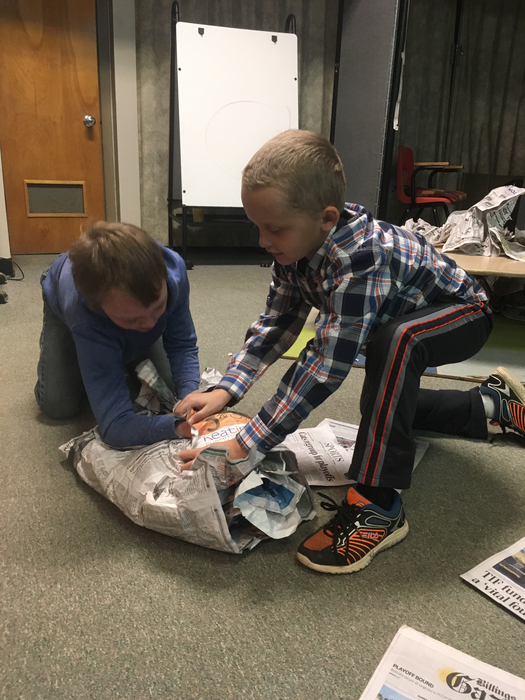 Two students use newspaper to make STEM snowmen.