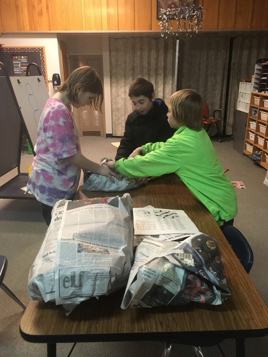 Three students use newspaper to make STEM snowmen.