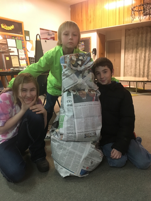 Three students pose with their newspaper snowman.