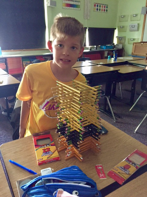 Student standing with a tower of pencils stacked log-cabin style.