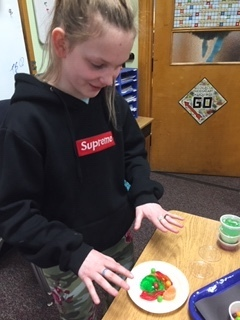 Student standing in front of a desk with a plate that has an edible cell creation.