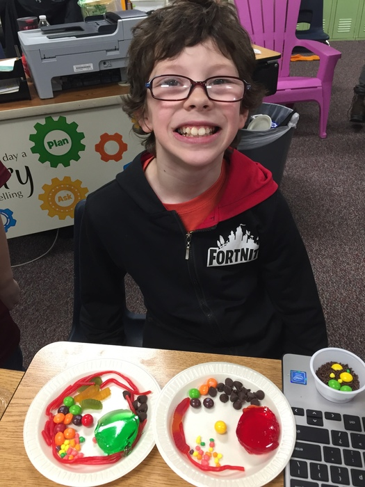 Boy with glasses smiling and sitting in front of his edible cell creation.