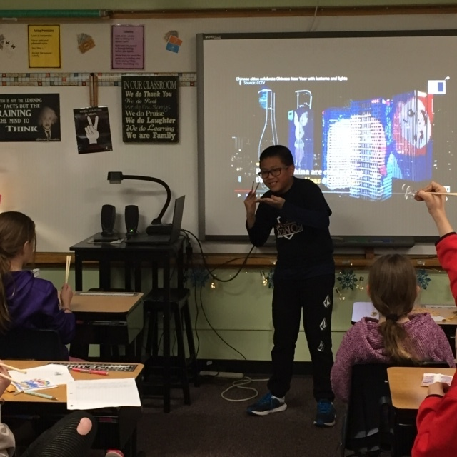 Student standing in front of a SmartBoard demonstrating how to hold chopsticks.