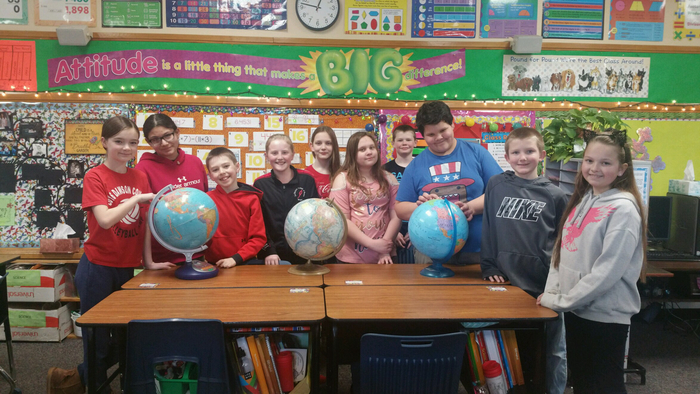 This is an image of ten 5th graders standing behind desks with 3 globes on them. They are the Lincoln School geography bee winners.