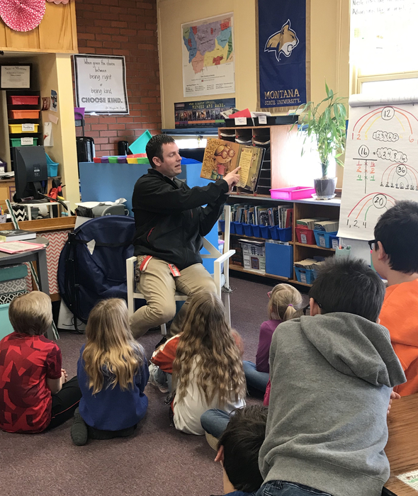 Mr. Schreibeis sitting in a chair reading a picture book to students sitting on the floor.