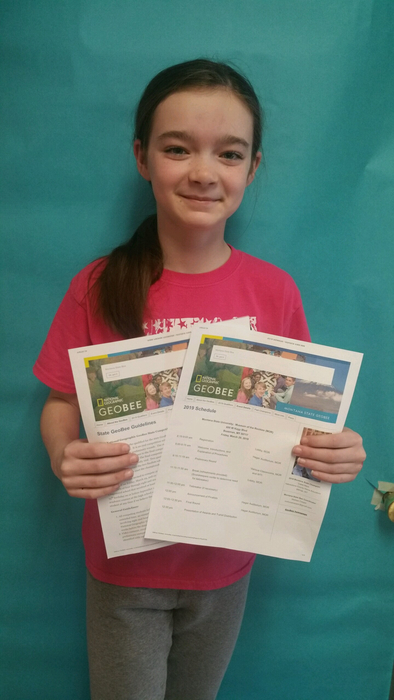 A student holding two papers about the Nat Geo Geography Bee she will be participating in.