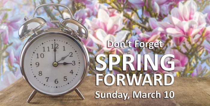 "Alarm clock in front of flowers with a message stating ""Don't Forget Spring Forward Sunday, March 10"""